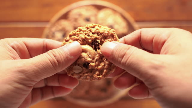 break cookies by hand to make eating easier. - attività del fine settimana video stock e b–roll