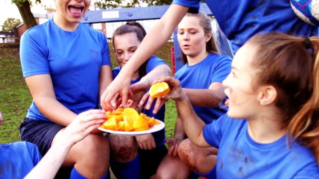 auszeit vom training und einige erfrischungen - teenage friends sharing food stock-videos und b-roll-filmmaterial