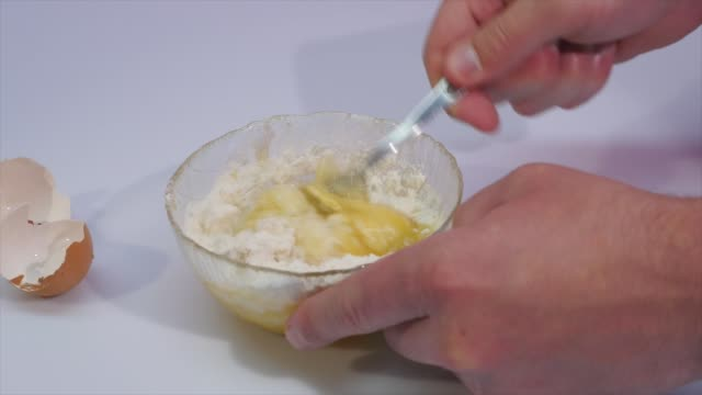 Break the egg in a bowl with flour video