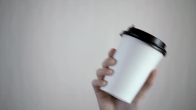 frühstück und kaffee thema: womans hand halten weiße leere kaffee pappbecher mit einer braunen kunststoff-kappe auf einem weißen hintergrund im studio, kaffee werbung - kaffeetasse stock-videos und b-roll-filmmaterial