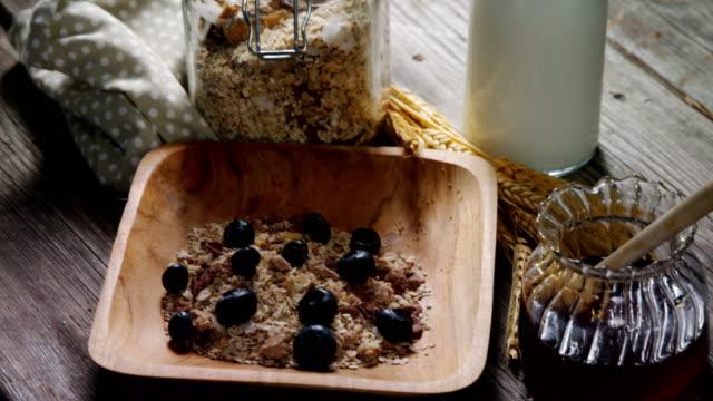 frühstückskost aus getreide und glas honig auf einem holztisch 4k - milchkrug stock-videos und b-roll-filmmaterial