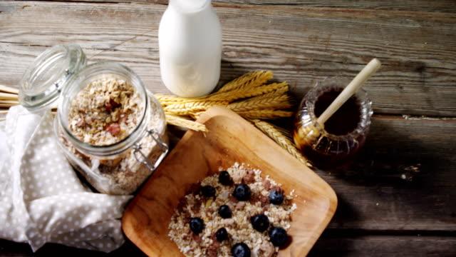 frühstückskost aus getreide und glas honig auf holztisch 4k - milchkrug stock-videos und b-roll-filmmaterial
