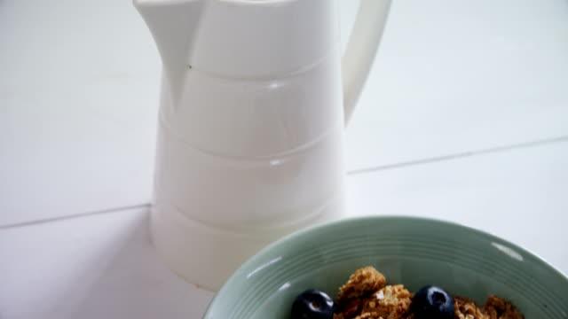 frühstückskost aus getreide in schüssel mit milchkännchen 4k - milchkrug stock-videos und b-roll-filmmaterial