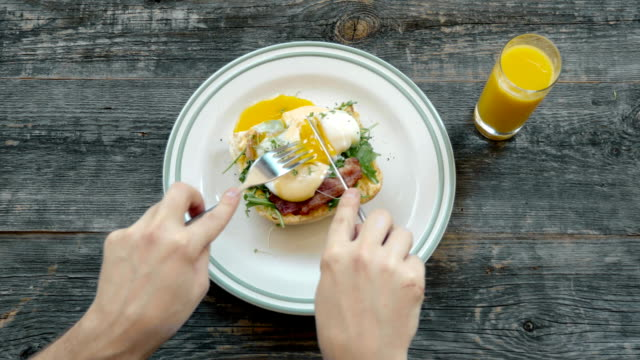 Breakfast - fried egg with bacon and cheese, top view in cafe with hands and fork video