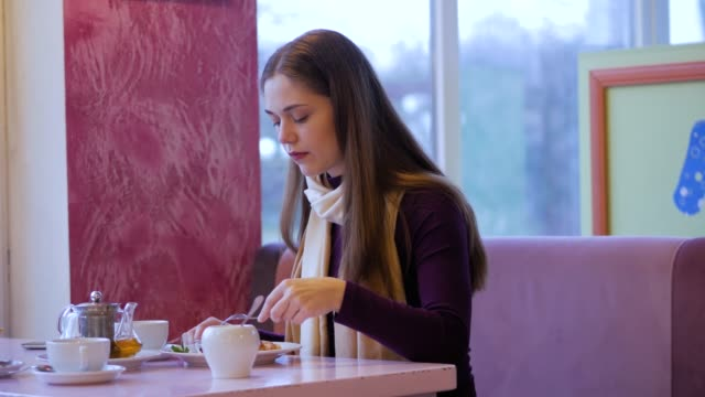 breakfast in a city cafe in the morning. a girl eating a cheese pancakes with jam and sour cream in restaurant. - pancake video stock e b–roll