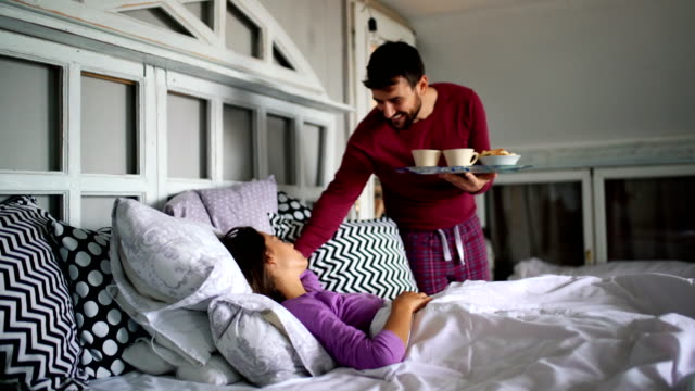 Breakfast in bed. Closeup of a mid 20's man bringing breakfast to his girlfriend while she's still asleep. She's happily waking up and kissing him. mid adult stock videos & royalty-free footage