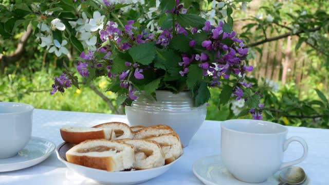 Breakfast in the spring garden on a table with a white tablecloth, served for a tea party