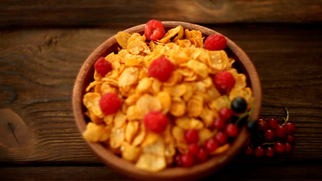 Breakfast of cornflakes with berries in wooden bowl video