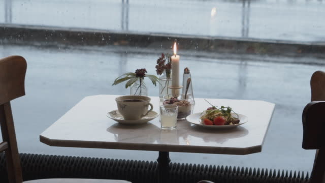 A breakfast on a lonely table at a café on a rainy day.