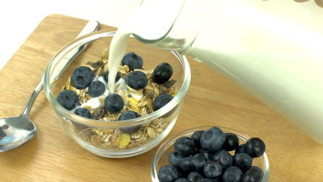Breakfast, Pour milk on cereal with blueberries on top, slow video