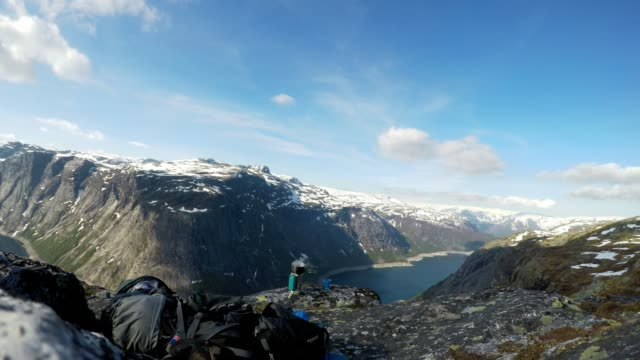 A breakfast set up in the tall mountains with a view on a fjord-like lake. Water is boiling in a portable stove for morning coffee. Clear and sunny weather. Camping in the wilderness. Snow caped fjord