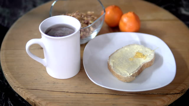 Breakfast time table. Spreading honey on on brioche bread with butter on wooden board with cup of tea