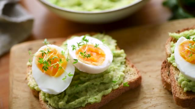 Breakfast toast with egg and avocado Breakfast toast with egg and avocado on breakfast table. Closeup view. HD footage avocado stock videos & royalty-free footage