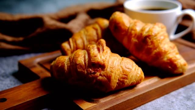frühstück mit frischen croissants und tasse schwarzem kaffee auf holzbrett - cappuccino stock-videos und b-roll-filmmaterial