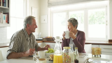 Breakfasts spent with you always taste a little bit sweeter 4k video footage of a happy senior couple having breakfast together inside their kitchen at home breakfast stock videos & royalty-free footage