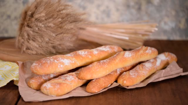 breaking a baguette. hands of woman breaking baked bread in half. woman hands breaking crispy french baguette - francuska kuchnia filmów i materiałów b-roll