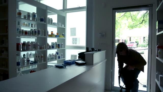 ломая стеклянную дверь розничного магазина - вор стоковые видео и кадры b-roll