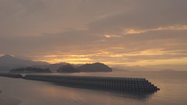 dalgakıran ve gün batımı - dalgakıran stok videoları ve detay görüntü çekimi