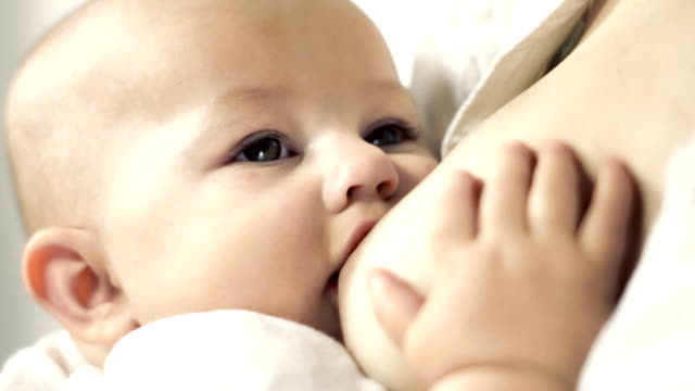 Breastfeeding a cute baby. High key video. video