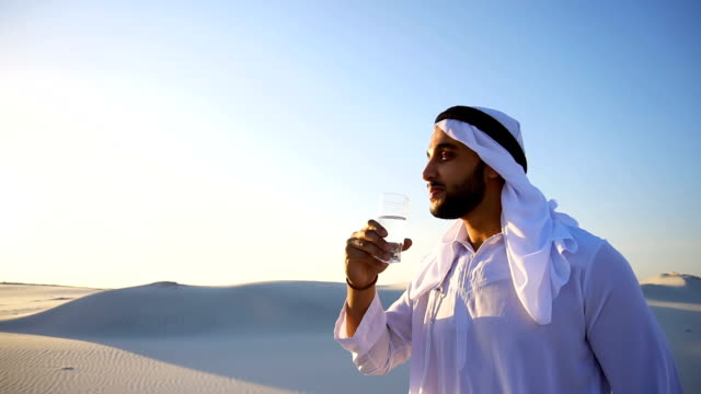 Breath of freshness of male Muslim in middle of dry climate of sandy desert. guy Arab drinks water from glass in open air in evening Stately Arab young man quenches thirst with glass of cool water and feels influx of strength and energy, smiles and looks to side, standing amidst endless sandy desert with pure white sand in open air on warm summer morning. Swarthy Muslim with short dark hair dressed in kandura, long, spacious dress made of white unpainted cotton with knitted lace cap of hafia, on top of which headscarf and dark brown shoes are tied. Concept of Arab and Muslim men, united Arab emirates and beautiful landscapes, hot climate and mineral water advertising, Emirates national clothes, good mood and happy emotions. thirsty stock videos & royalty-free footage