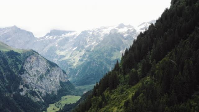 Breathtaking aerial background shot of beautiful green mountains revealing snowy peaks landscape in Switzerland Alps.