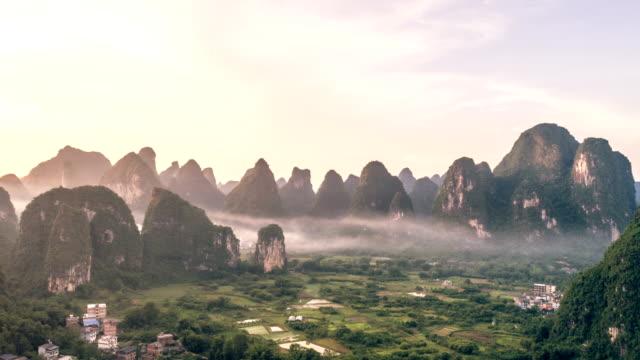 atemberaubende luftaufnahmen einspielung über schöne kalkstein karst gebirgslandschaft, bei sonnenuntergang in yangshuo county,china.mountain landschaft draufsicht mit dunst bedeckt. - südwesten stock-videos und b-roll-filmmaterial