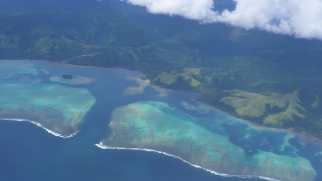 AERIAL SLOW MOTION: Breathtaking view of Fiji island and endangered coral reefs. AERIAL SLOW MOTION: Cinematic view of the Fiji Island landscape and beautiful corals. Tropical vacation in stunning seaside setting. Global warming and its devastating effect on natural environment. pacific islands stock videos & royalty-free footage