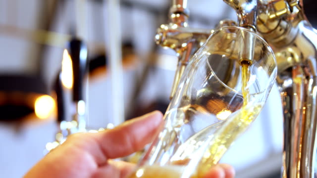 Brewer filling beer in beer glass from beer pump 4k - video