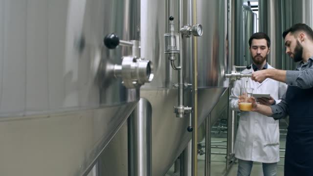 ながら注ぐビール醸造技術者に指示する従業員 - 醸造所点の映像素材/bロール