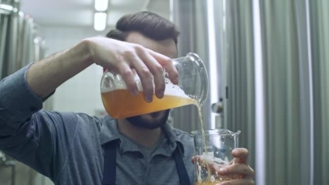 醸造所の監督測定ビールと水差しを見て - 醸造所点の映像素材/bロール