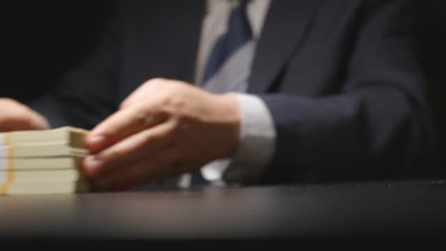 vídeos de stock e filmes b-roll de bribe: businessman gives a money bundle on a table at negotiation time (hidden cam) - corruption