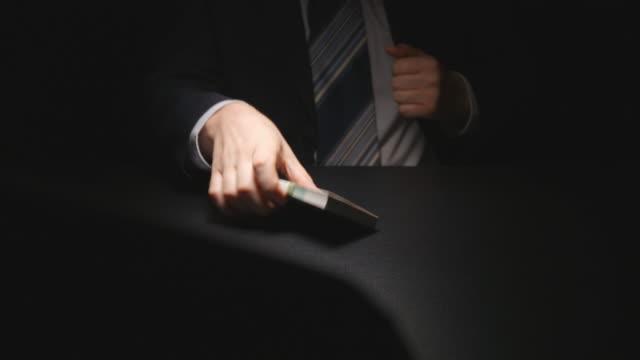 muta: affärsman tar en bunt med pengar från en tabell och sätter i en kostym på förhandlingstid (euro) - kriminell bildbanksvideor och videomaterial från bakom kulisserna