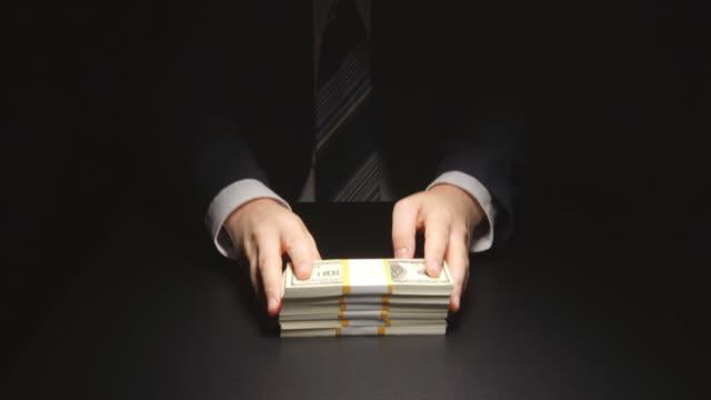 vídeos de stock e filmes b-roll de bribe: businessman waits and puts a heap money on a table - corruption