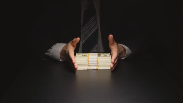 vídeos de stock e filmes b-roll de bribe: businessman waits, touches a money bundle and gives it - corruption
