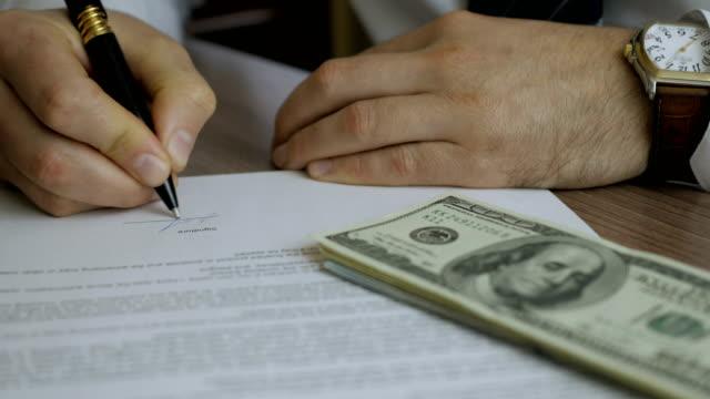 贈収賄と汚職の概念は、ドル紙幣の形で賄賂、ビジネスマンは不動産契約や金融企業との契約を締結しながらお金を取ります。 - 腐敗点の映像素材/bロール