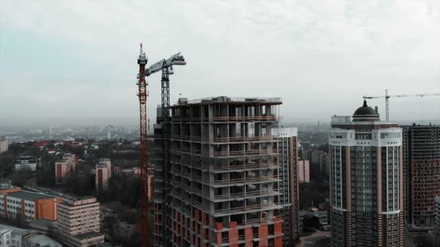 tegel och betong vid anläggningsarbeten. aerial drone syn på höghus bostadskomplex konstruktion. hög kran nära oavslutad byggnad - stenhus bildbanksvideor och videomaterial från bakom kulisserna