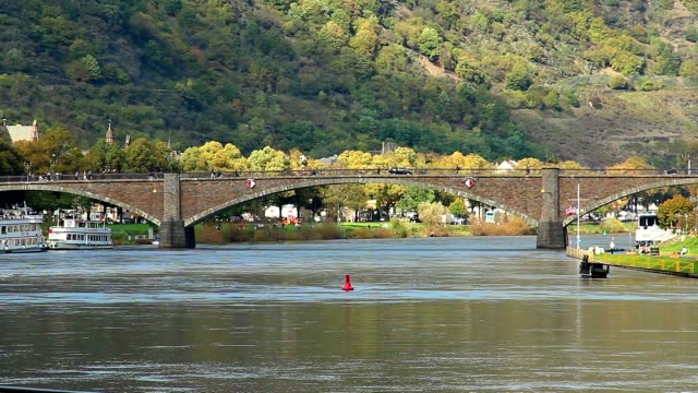 Brick bridge over river, car traffic, green hills people walking. Beautiful shot of Europe, culture and landscapes. Traveling sightseeing, tourist views landmarks of Germany. World travel, west European trip cityscape, outdoor shot video