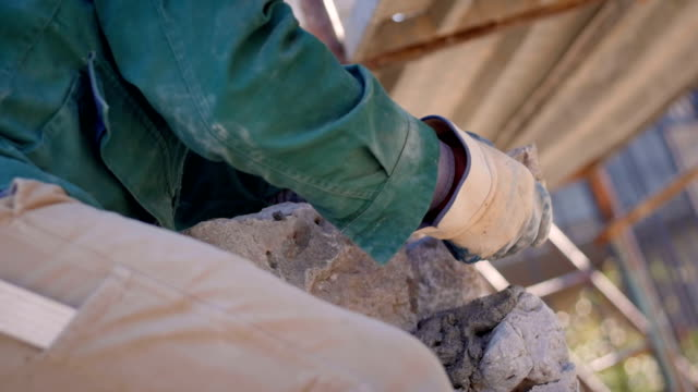 Bricklayer's hands placing stones on a wall video