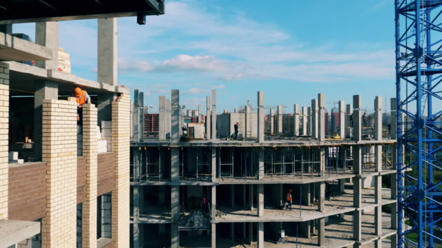 Bricks and concrete building is being constructed Bricks and concrete building is being constructed. 4K foundation make up stock videos & royalty-free footage