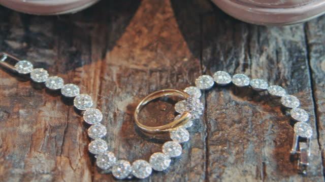 свадебные аксессуары, браслет лежит на деревянной поверхности - браслет стоковые видео и кадры b-roll