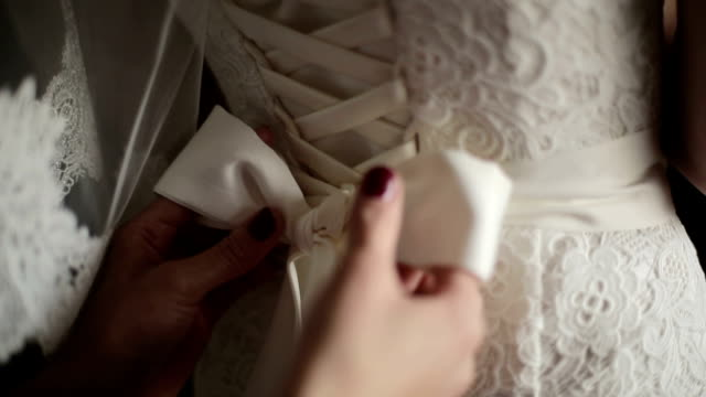 Bridal corset is being tied up video