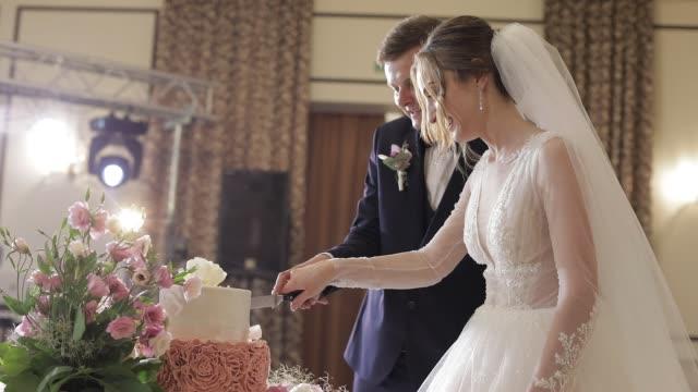 vidéos et rushes de mariée et un marié est la coupe de leur gâteau de mariage. les nouveaux mariés coupent une tranche de gâteau - banquet