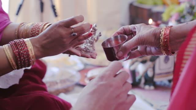 sposa e sposo che tamponano la polvere sulla statua religiosa come parte della loro cerimonia nuziale indù. - costume tradizionale video stock e b–roll