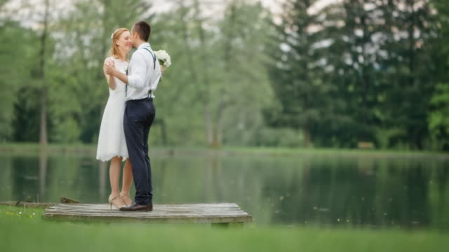 SLO MO Bride and groom dancing by the lake video