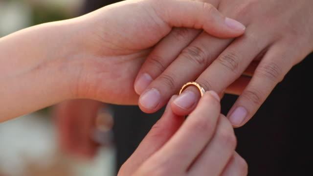 sposa e sposo che si scambiano fedi nuziali in cerimonia nuziale. - mano donna dita unite video stock e b–roll