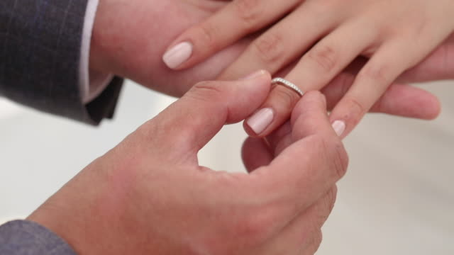 Bride and groom exchanging wedding rings in wedding ceremony.