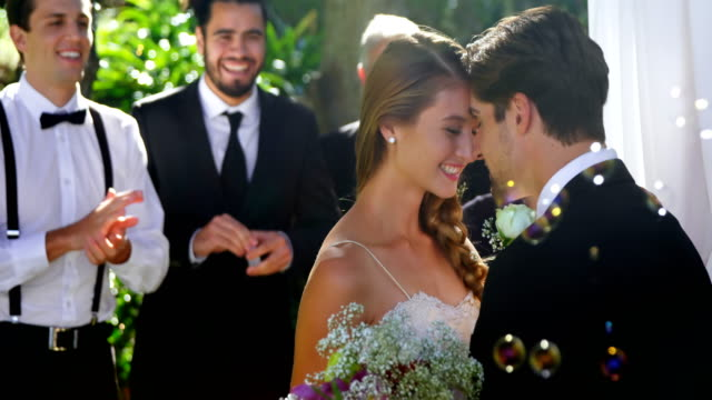 bride and groom happily hugging each other and guests clapping 4k 4k - matrimonio video stock e b–roll