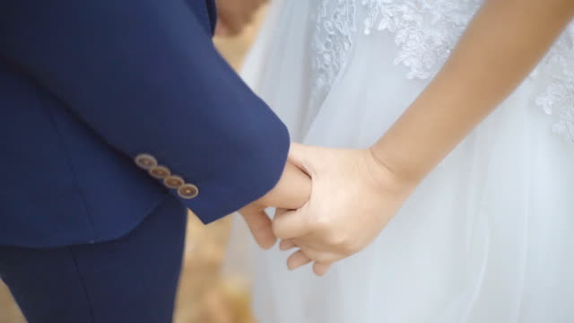 Bride and Groom holding comforting hand together in the park. video