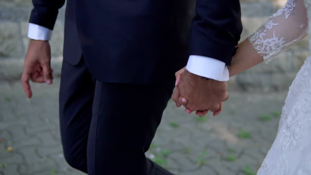 bride and groom holding hands and walking - matrimonio video stock e b–roll