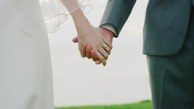 bride and groom holding hands - matrimonio video stock e b–roll